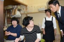 「野菜百楽」の厨房で働く様子を見学する細野幹事長