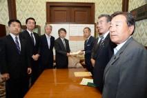 参院事務総長に法案を手渡す6党の提出者たち