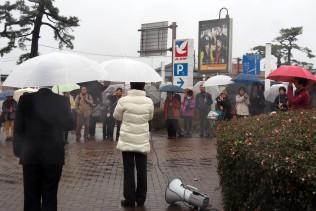 風雨の強まる中、足を止めて演説を聞く人々